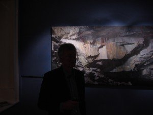 Adventurously, some paintings are spotlit in a darkened room, which suits them perfectly. Cooper silhouetted here against 'Sawyer's Wood'